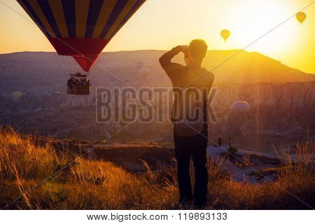 man taking picture of Hot air balloons flying over spectacular Cappadocia