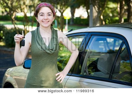 Pretty teen girl holding up the keys to her new car.