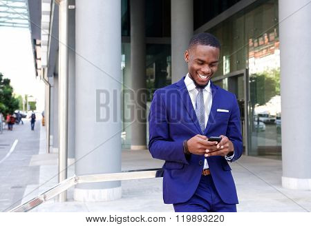 African Business Man Walking And Looking At Mobile Phone