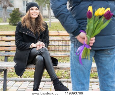 Young Woman Sits On A Bench And Looks At The Man Standing Next To Her, Man Which Gives Her A Bouquet