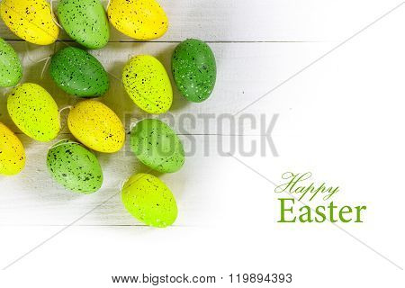 Green And Yellow Easter Eggs On White Wood, Isolated Corner Background, Text Happy Easter