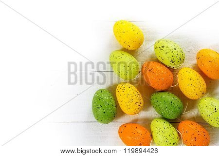 Easter Eggs In Green, Yellow And Orange On White Wood, Corner Background, Copy Space