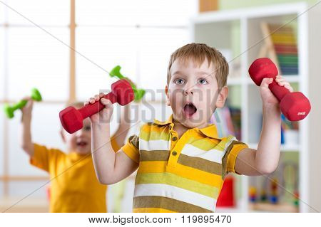 Funny kids boys exercising with dumbbells. Healthy life, sportive children.