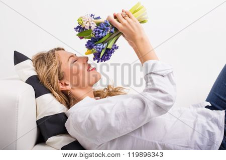 Woman lying on couch and smelling flowers