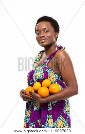 Beautiful smiling african american young woman in colorful sundress standing and holding oranges and lemons over white background