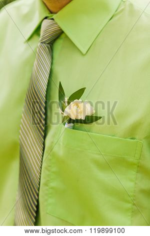 White rose boutonniere on green suit of the groom