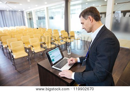 Concentrated speaker in black suit standing at the tribune and using laptop in empty meeting hall