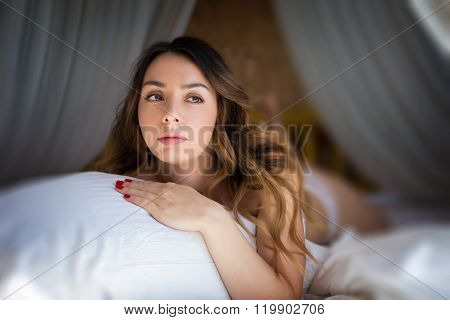 Girl in bed hugging a pillow