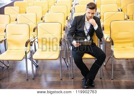 Concentrated businessman working with tablet in empty conference hall