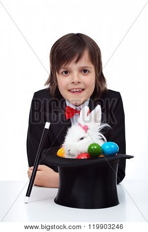 Easter magic - boy pulling a grumpy rabbit and colorful eggs from the magician hat
