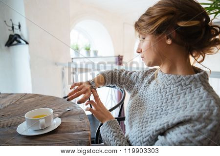 Young woman sitting on the table with cup of tea and looking on wrist watch in restaurant