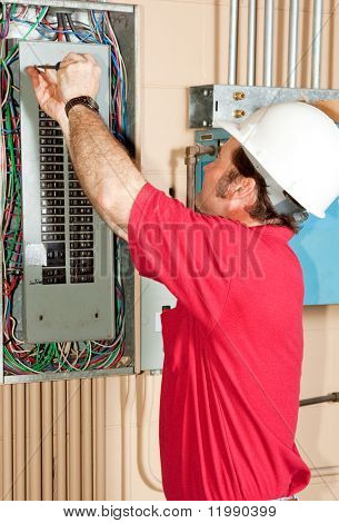 Licensed master electrician working on an industrial breaker panel.