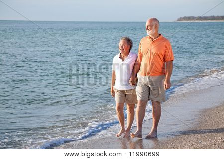 Happy senior couple enjoys a romantic stroll on the beach.