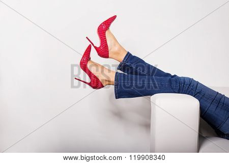 Female legs in jeans and red high heels