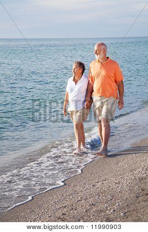 Retired senior couple takes a romantic stroll on the beach.
