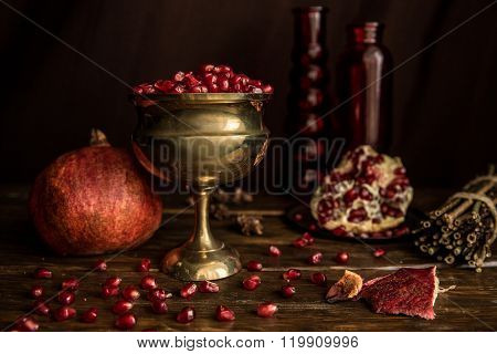 Pomegranate grains in an iron vase on a dark wooden board