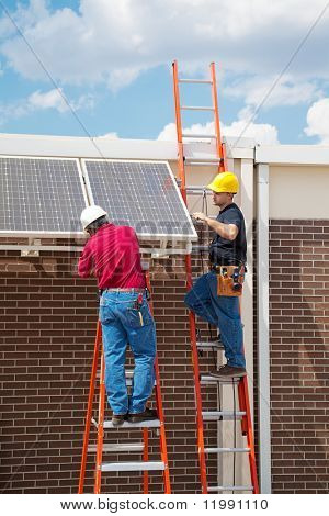 Two workers installing solar panels on the side of a building.  Vertical with room for text.
