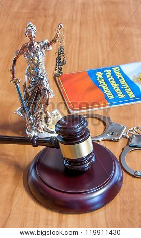 Statuette of Themis gavel vaults the Constitution of the Russian Federation and handcuffs on the table