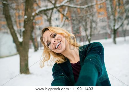 Blond woman taking selfie outside in winter nature