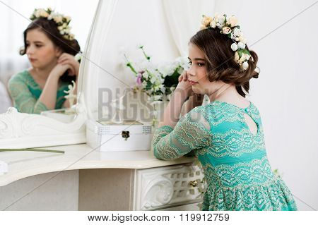 Little Pensive Girl In Flower  Wreath Is Sitting At The Dressing Table