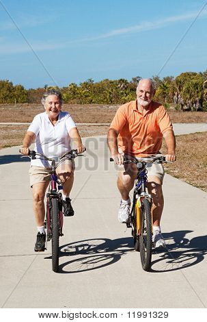 Senior couple has fun riding their bicycles on a tropical vacation.