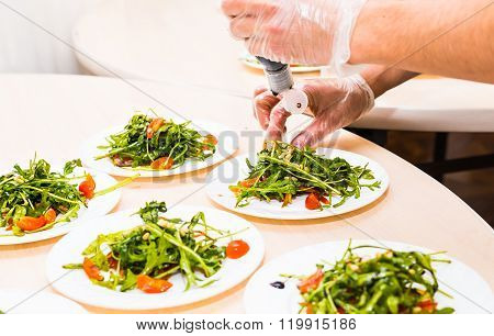 Process of preparing sauce for salad, at kitchen. Man pouring sauce into plate with salad ingredient