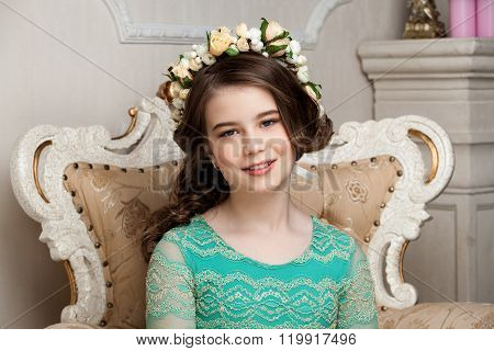 Portrait Of A Smiling Little Girl In The Flower Wreath Sitting On The Chair, Smiling