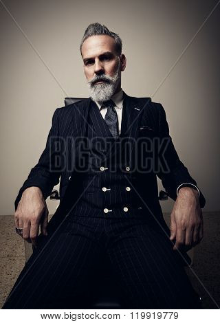 Portrait of serious adult businessman wearing trendy suit and sitting studio on chair against the em