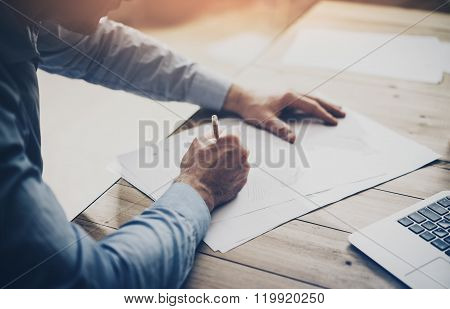 Working process. Businessman working at the wood table with new project . Generic design notebook on