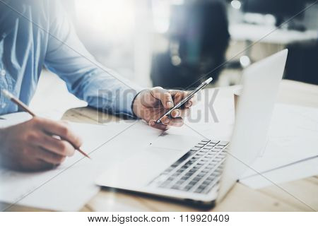 Businessman in workplace. Texting message smartphone and holding pencil hands. Generic design notebo