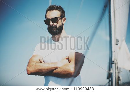 Portrait of young bearded man standing on the yacht, wearing sunglasses in sunny day. his arms are c