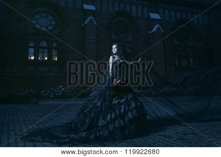 Mysterious woman in black dress near chirch