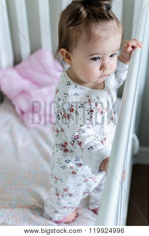 Portrait Of Adorable Little Baby Girl Staying At Her Bed In Full-length