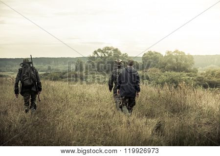 group of people  going up in the early morning in a rural field through the tall grass during hunting