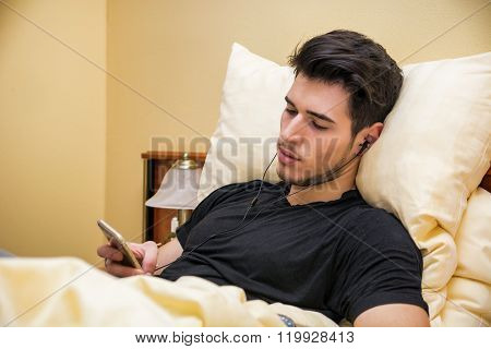 Handsome young man in bed listening to music