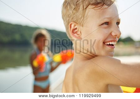 Happy boy at a lake with a squirt gun in summer