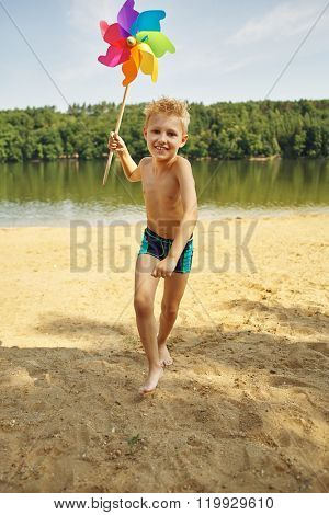 Happy boy on the sand playing with a windmill in summer