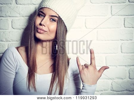 Portrait of young attractive cheerful hipster girl making funny faces, studio shot over white bricks background. Image toned