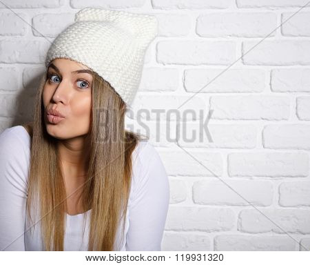 Portrait of young attractive cheerful hipster girl making funny faces, studio shot over white bricks background.