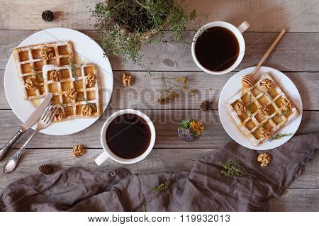 Waffles with honey, nuts, coffee and herbs, sweet dessert breakfast.