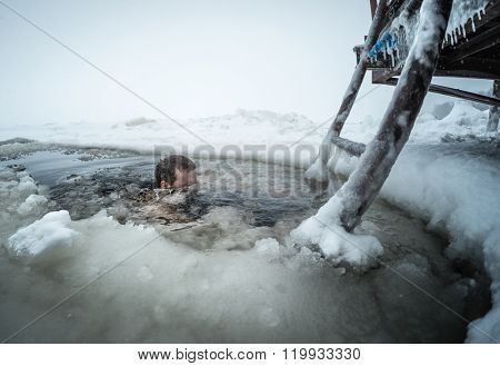 Young man swimming in the ice hole on a winter lake