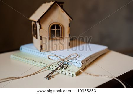 Conceptual image with small wooden house and keys