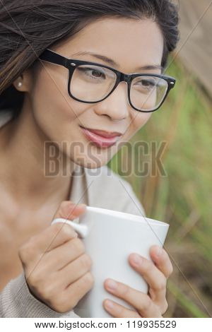 Beautiful young Asian Chinese woman or girl wearing glasses, outside, smiling and drinking a cup of coffee or tea