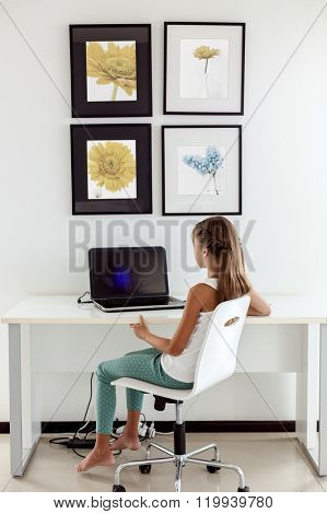 Tween girl using laptop at the table in the room