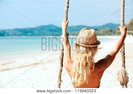 Girl sitting on the swing on the tropical beach, paradise island