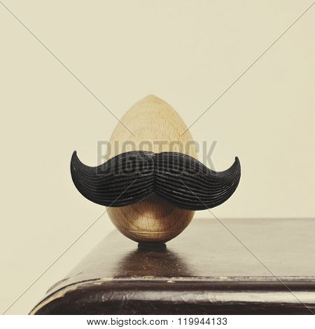 closeup of a mustached wooden egg, on an old wooden piece of furniture