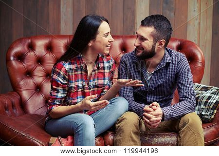 smiley couple sitting on couch and have a nice conversation at home