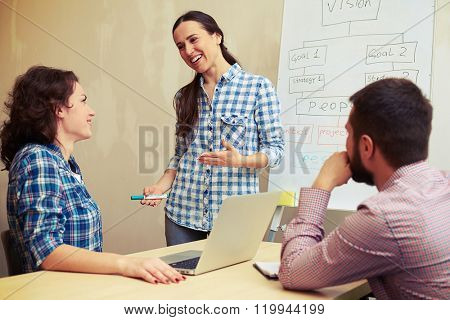 young woman standing hear flipchart and telling something to her colleagues