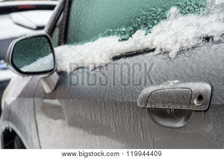 Car handle mirror and window are covered with ice after freezing rain