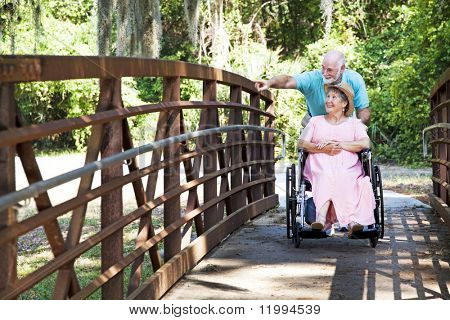 Senior man pushes his disabled wife's wheelchair through the park.